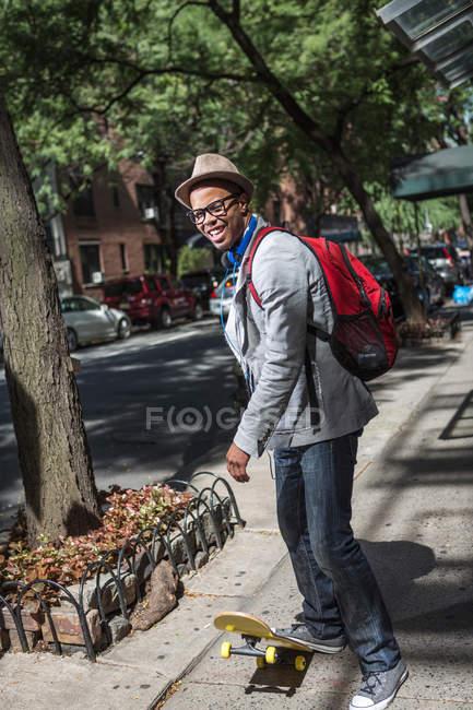 Jeune homme en planche à roulettes sur le trottoir — Photo de stock