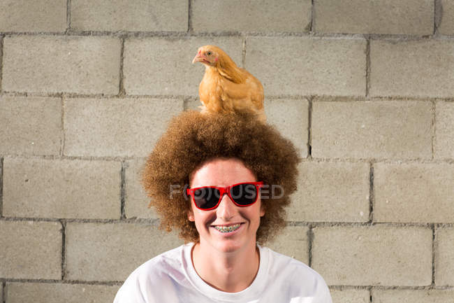 Portrait of teenage boy with red afro hair, chicken sitting on head — Stock Photo