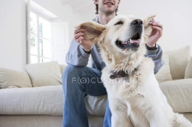 Junger Mann auf Sofa im Wohnzimmer halten die Ohren der golden Retriever Hund — Stockfoto