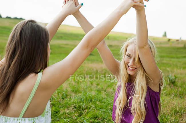 Молодые женщины с поднятыми и руки — стоковое фото
