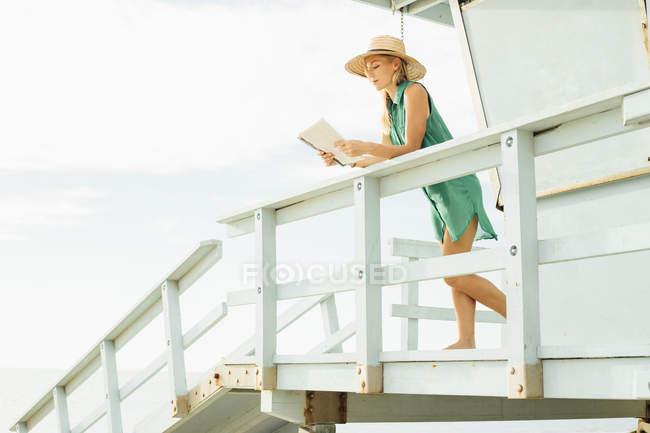 Portrait d'une femme dans un chapeau et des lunettes assis au bord de la fenêtre sur le toit — Photo de stock