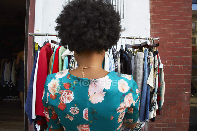 Rear view of young fashion blogger with afro hair looking at vintage clothes rail, New York, USA — стоковое фото