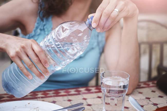 Обрізаний знімок зрілої жінки розливу склянку воду в пляшках на стіл — стокове фото