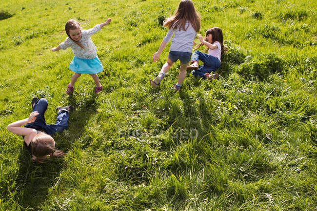Girls playing together in field — стокове фото