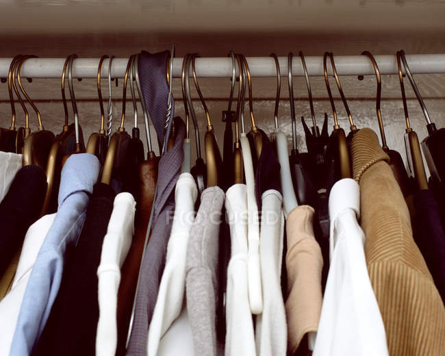 Clothes hanging in cupboard — Stock Photo