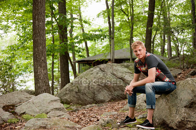 Portrait of mid adult man sitting in forest — Stock Photo
