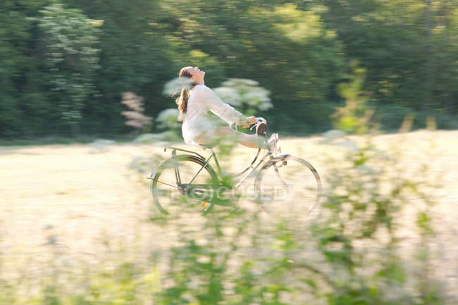 Woman cycling through countryside — Stock Photo