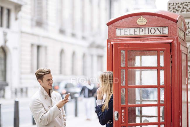 Young couple with smartphone next to red phone box, London, England, UK — Stock Photo
