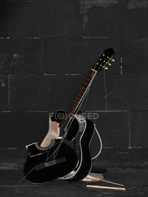 Smashed acoustic guitar beside black wall — Stock Photo