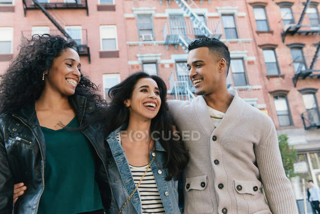 Three mid adult friends with arms around each other in city street — Stock Photo