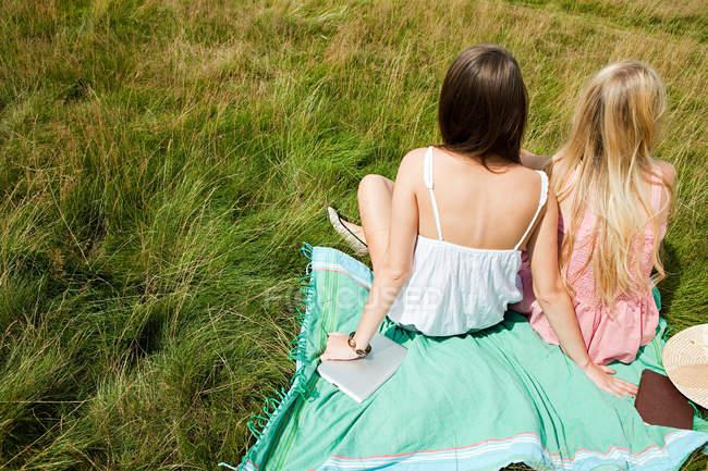 Jovens mulheres sentadas juntas em um campo — Fotografia de Stock