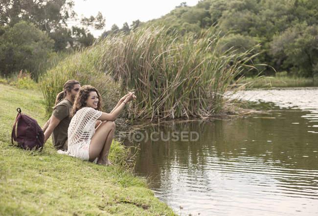 Пара, сидя у реки глядя прочь улыбается, — стоковое фото