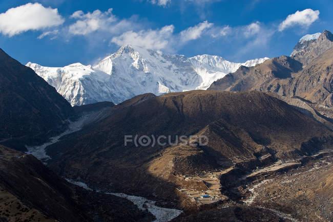 Заснеженные горы возле долины при ярком солнечном свете — стоковое фото