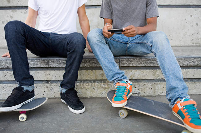 Teenage boys with skateboards and cellphone — Stock Photo