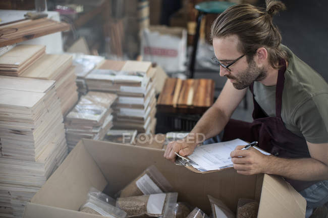 Man with clipboard checking boxed products in factory — Stock Photo
