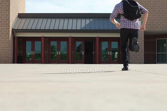 Studente di liceo maschile che corre verso la scuola — Foto stock