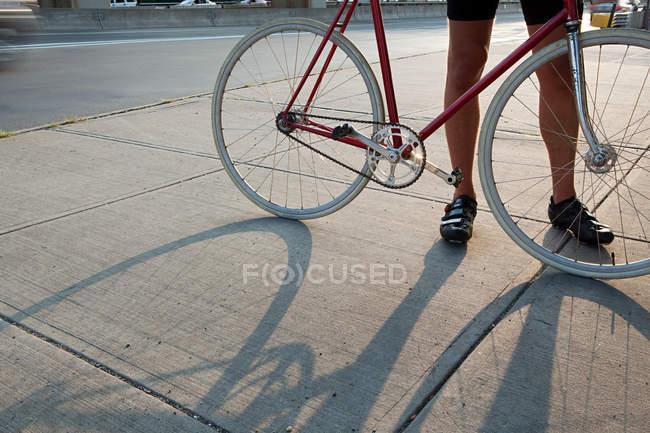 Кадроване зображення велосипедист стоячи з велосипеда на вулиці — стокове фото