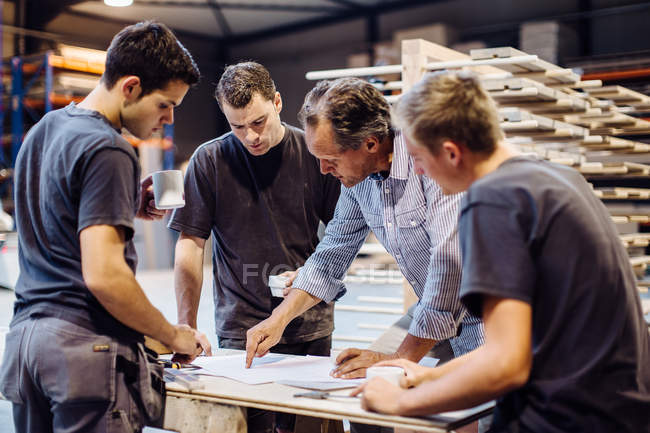 Male carpenter explaining blueprint to trainees in workshop — Stock Photo
