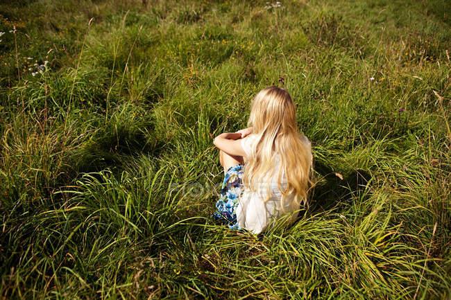Junge Frau sitzt friedlich in einem Feld — Stockfoto