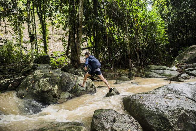 Young man crossing stream, Secret Buddha Garden, Koh Samui, Thailand — Stock Photo