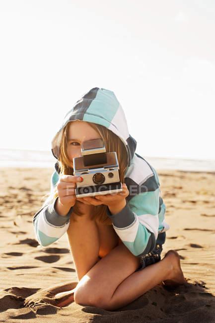 Девушка с мгновенной камерой на пляже — стоковое фото