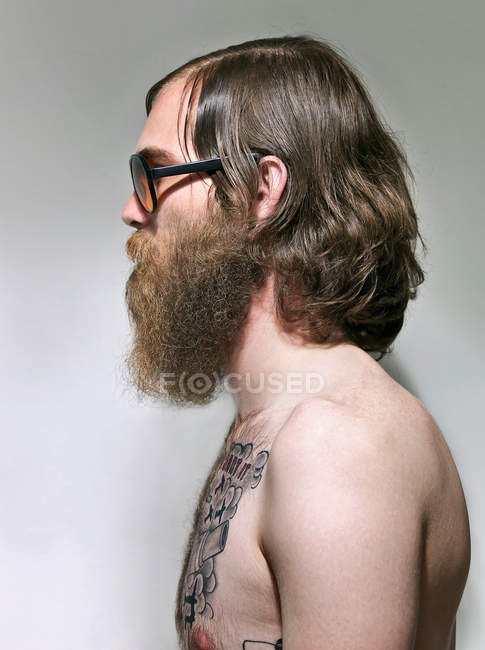 Young man with beard and tattoos on chest, side view — Stock Photo