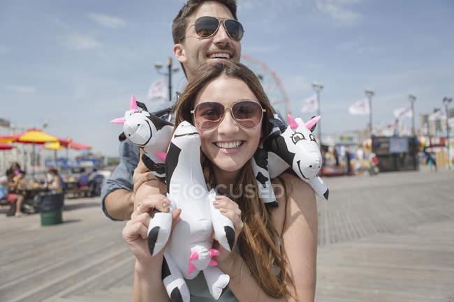 Couple contemporain s'amuser sur la promenade du parc d'attractions avec sauter prix — Photo de stock