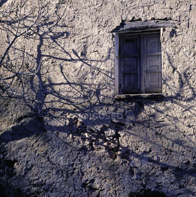 Janela fechada na parede de pedra com sombras — Fotografia de Stock