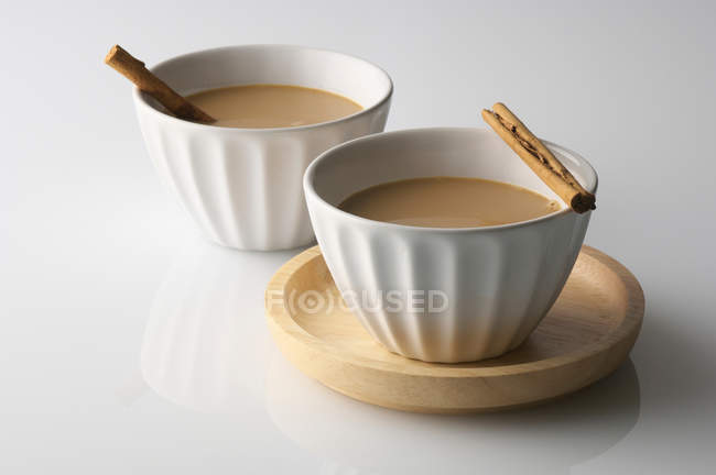Two bowls of drink with cinnamon sticks — Stock Photo