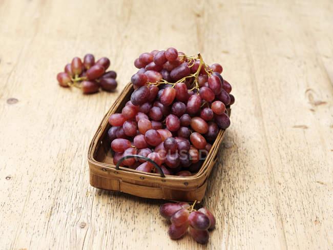 Uve rosse in cestino di vimini dell'annata su legno — Foto stock