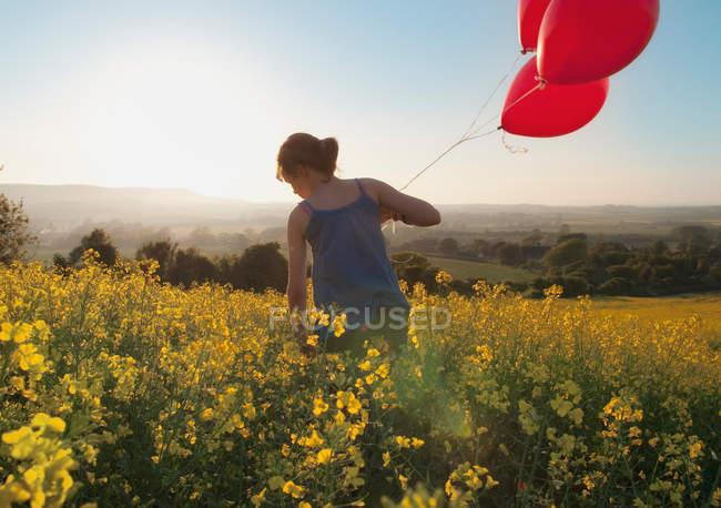 Дівчина проведення повітряних куль в поле — стокове фото