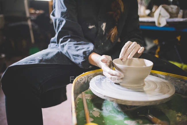 Young woman sitting at pottery wheel making clay pot — Stock Photo