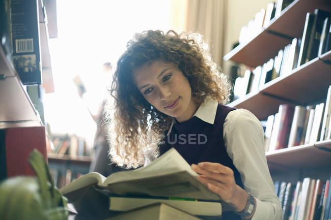 Libro di lettura degli studenti in biblioteca — Foto stock
