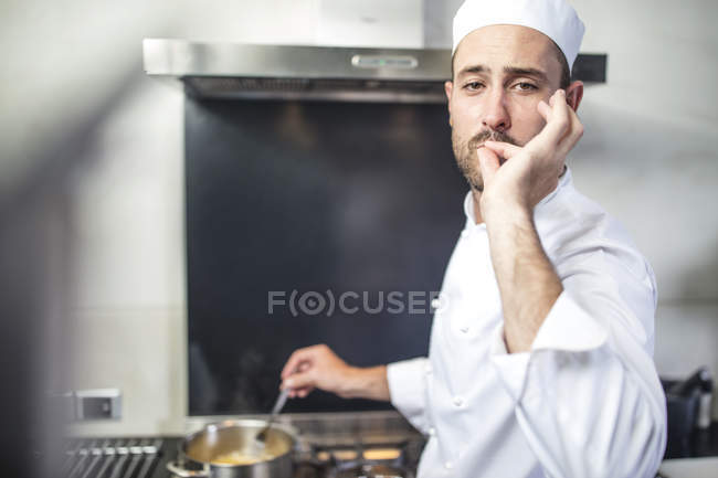 Portrait of chef stirring pan on stove, signalling with fingers to lips — Stock Photo