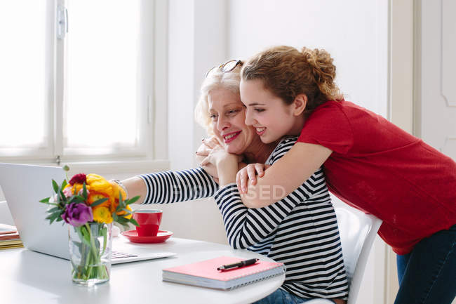 Mother and teenage daughter looking at laptop at home — Stock Photo