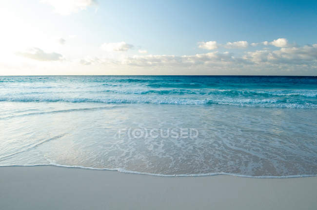 Surf waves on sandy shore under cloudy sky — Stock Photo