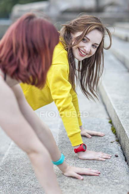 Молода жінка робить віджимання на дії. — стокове фото