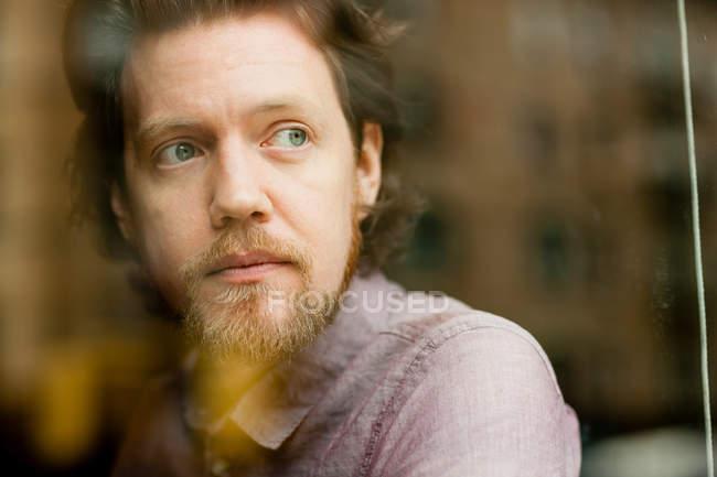 Портрет людина дивиться з вікна — стокове фото