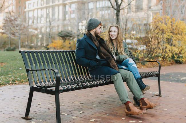 Young couple resting on park bench, Boston, Massachusetts, USA — Stock Photo
