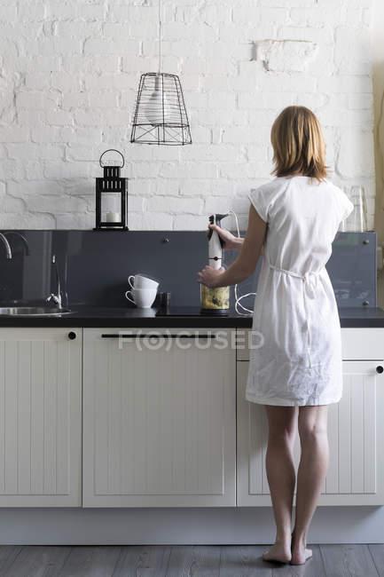 Задній вид жінки на кухонному блендері. — стокове фото