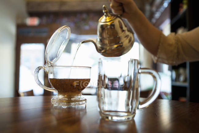 Female hand pouring tea on cafe counter — Stock Photo