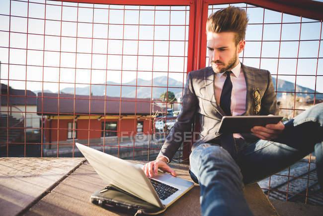 Stylish young man sitting on footbridge using laptop and digital tablet — Stock Photo