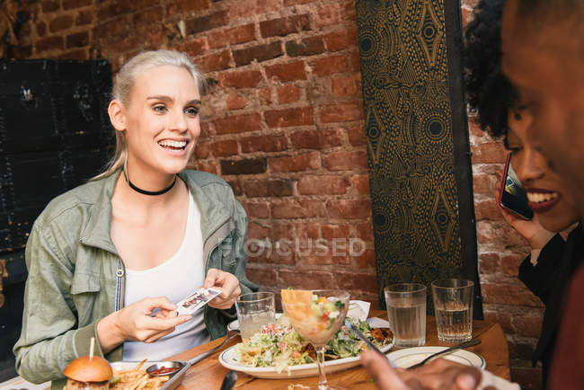 Multicultural Friends sharing meal together in cafe — Stock Photo