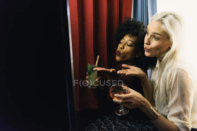 Multicultural Women using photo booth and blowing kisses — Stock Photo