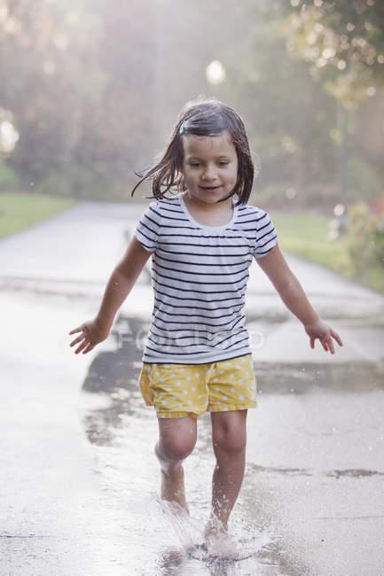 Barefoot girl running through puddles on rainy street — Stock Photo