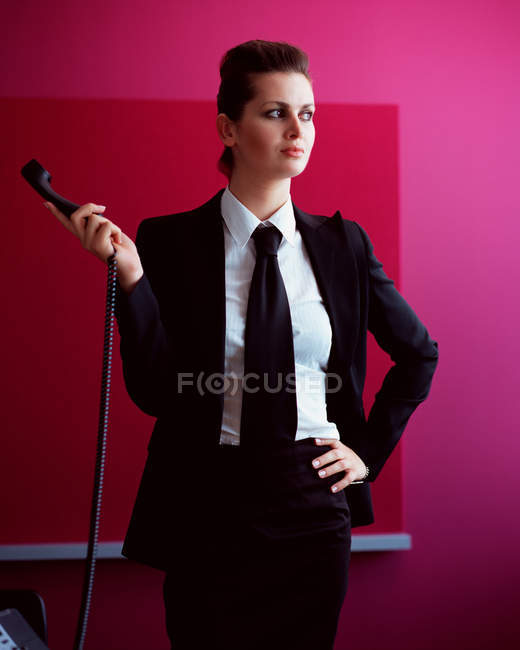 Businesswoman holding a telephone handset — Stock Photo