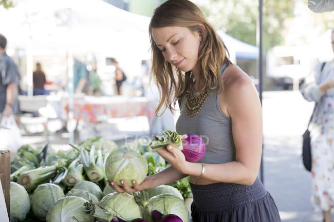 Mujer en puesto de frutas y verduras seleccionando cebollas rojas - foto de stock