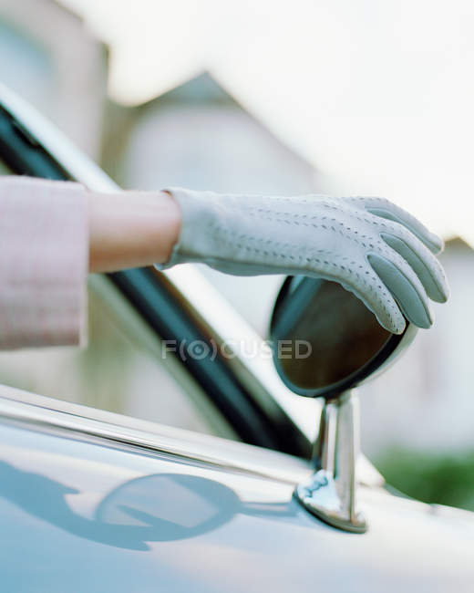 Female hand wearing glove adjusting rearview mirror — Stock Photo