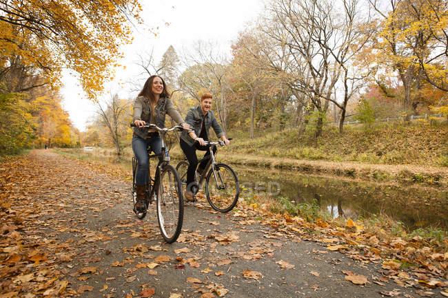 Heureux jeune couple à vélo le long de la rivière en automne — Photo de stock