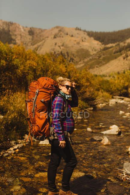 Retrato de una mujer embarazada con mochila, Mineral King, Sequoia National Park, California, EE.UU. - foto de stock